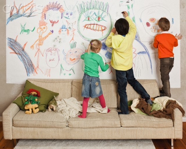 Little kids drawing on a wall